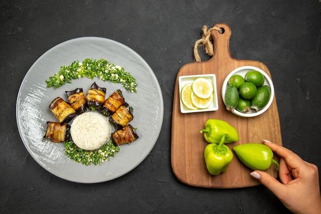 Vista dall'alto deliziose melanzane cotte con riso limone e feijoa sulla superficie scura cena cibo olio da cucina farina di riso