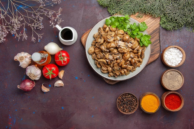 Top view delicious cooked mushrooms with seasonings and vegetables on dark background meal dish dinner wild plant food