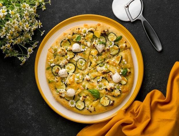 Vista dall'alto di una deliziosa pizza cotta con fiori di camomilla e tagliapizza