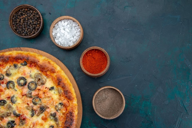 Top view of delicious cooked pizza with different seasonings on the dark blue desk