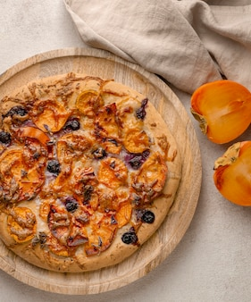 Top view of delicious cooked pizza with persimmons