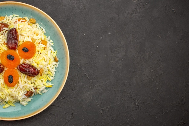 Vista dall'alto del delizioso riso plov cotto con uvetta diversa all'interno della piastra sulla superficie grigio scuro