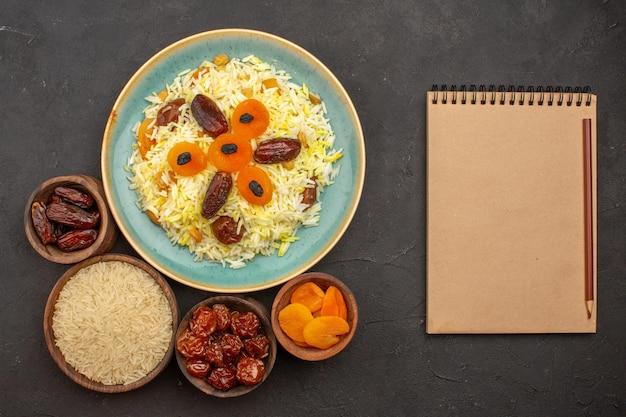 Vista dall'alto del delizioso riso plov cotto con uvetta diversa all'interno del piatto sulla superficie grigia