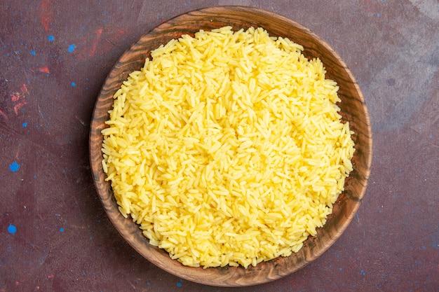 Вид сверху вкусного вареного риса внутри коричневой тарелки на темном столе