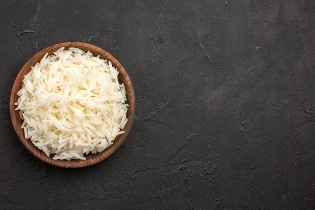 Top view delicious cooked rice plain tasty rice inside brown plate on the dark space