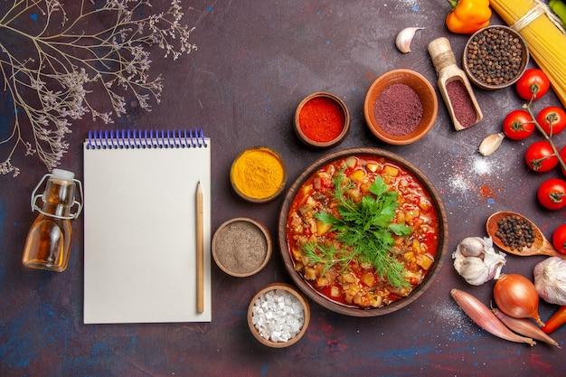Vista dall'alto deliziose verdure cotte affettate con diversi condimenti sulla salsa di cibo pasto zuppa sfondo scuro