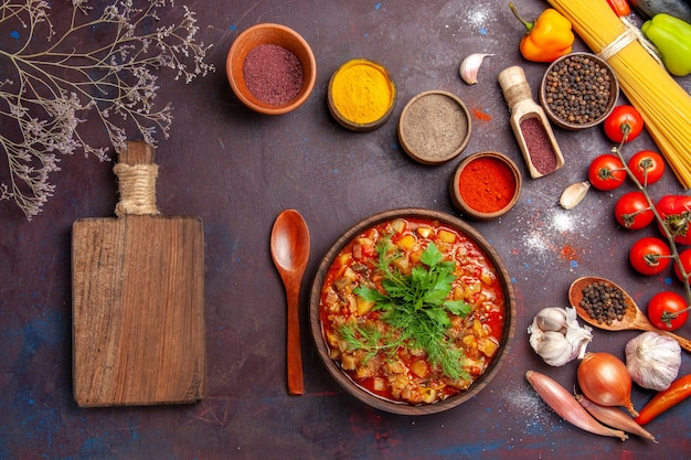 Vista dall'alto deliziose verdure cotte affettate con diversi condimenti sul piatto scuro della zuppa di cibo salsa pasto vegetale