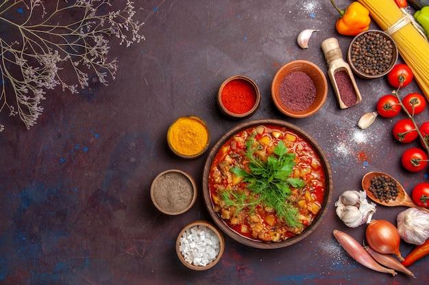 暗い背景にさまざまな調味料でスライスしたおいしい調理済み野菜の上面図スープミールフードソース