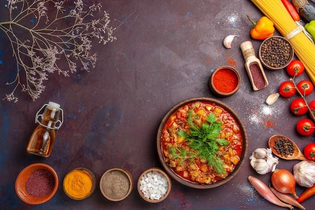 トップビューダークデスクスープミールフードソースでさまざまな調味料でスライスされたおいしい調理野菜