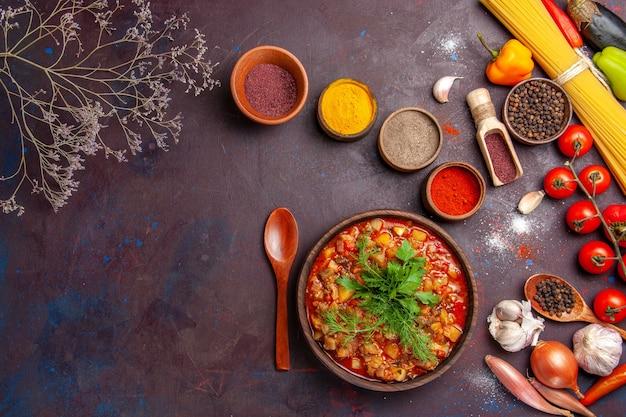 暗い背景にさまざまな調味料でスライスしたおいしい調理済み野菜の上面図スープフードソース食事野菜