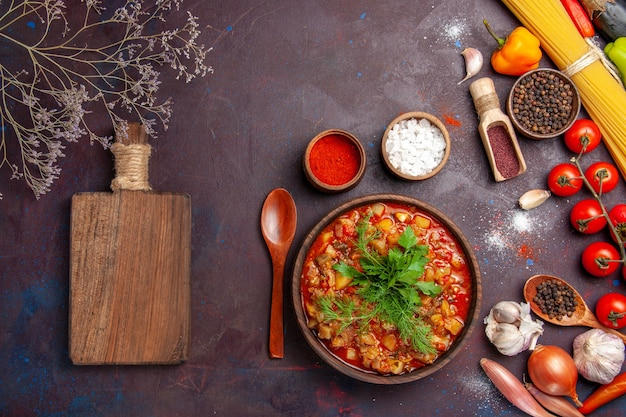 暗い背景に緑と調味料でスライスしたおいしい調理済み野菜の上面図スープミールフードソース