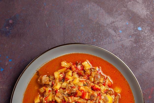 Vista dall'alto deliziose verdure cotte affettate con salsa su sfondo scuro zuppa di salsa di cibo vegetale