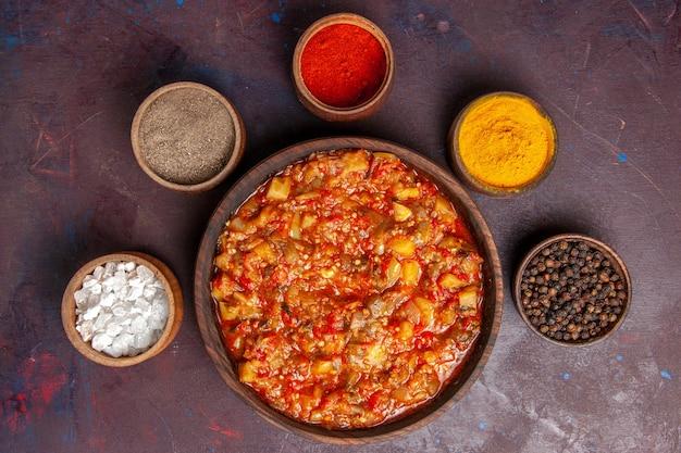 暗い背景にさまざまな調味料を使ったおいしい調理野菜の上面図スープソースミール野菜料理