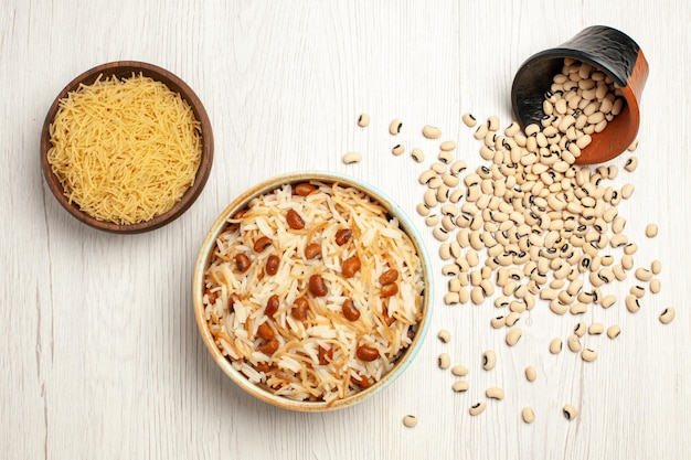 Vista dall'alto deliziosi vermicelli cotti con fagioli su un pasto di fagioli da scrivania bianco chiaro che cucina un piatto di pasta