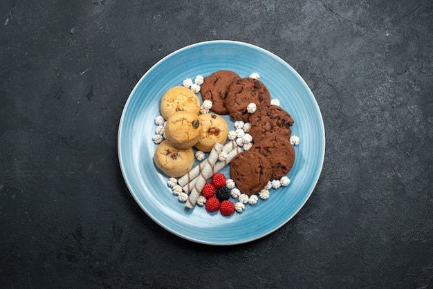 Top view delicious cookies chocolate and simple ones with candies on dark grey surface sugar biscuit cake sweet cookie