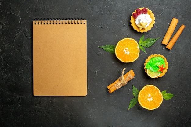 Top view of delicious cookies cinnamon limes and half cut oranges with leaves and notebook on dark background
