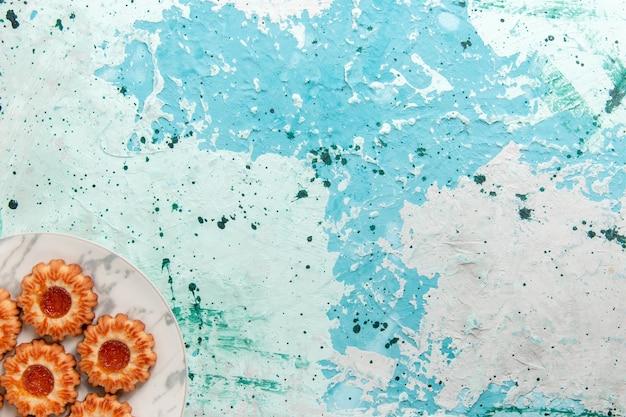 Vista dall'alto deliziosi biscotti tondi formati con marmellata all'interno della piastra sullo sfondo azzurro biscotto zucchero dolce torta biscotto