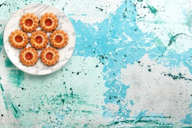 Vista dall'alto deliziosi biscotti tondi formati con marmellata all'interno della piastra sullo sfondo azzurro biscotto zucchero dolce biscotto pasta torta cuocere