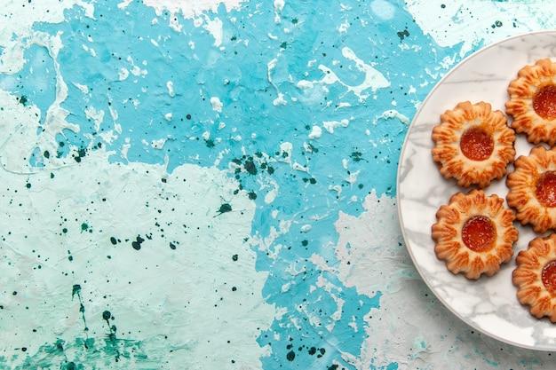 上面図水色の机の上のプレートの内側にジャムで形成されたおいしいクッキーラウンドクッキーシュガースイートビスケット生地ケーキ焼き