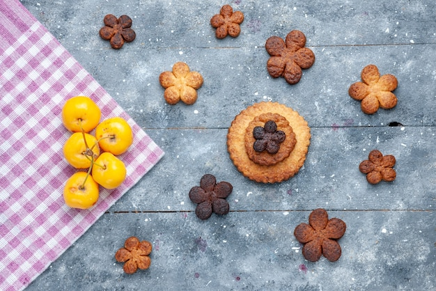 Top view of delicious cookies sweet spread all over the wooden grey, with yellow cherries cookie sugar biscuit sweet
