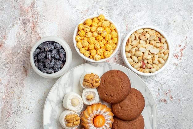 上面図白い背景の上のキャンディーとナッツのおいしいクッキービスケット甘いケーキクッキーナッツ
