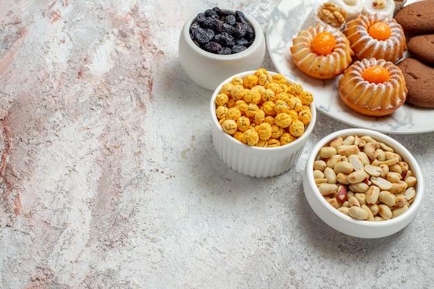上面図白い背景の上のキャンディーとナッツのおいしいクッキーケーキクッキービスケット甘い砂糖茶
