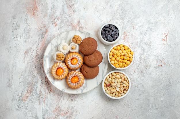 Вид сверху вкусное печенье с конфетами и орехами на белом фоне, сладкий торт, печенье, бисквит, орех