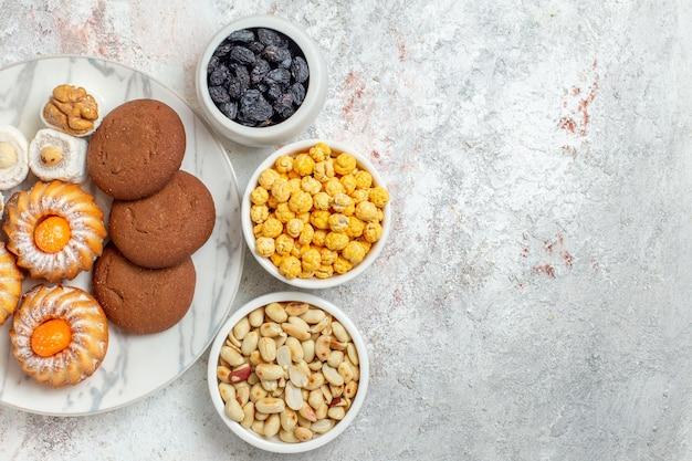 Вид сверху вкусное печенье с конфетами и орехами на белом фоне, сладкий торт, печенье, печенье, сахар, чай
