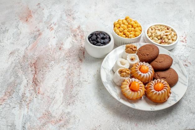 上面図白い背景の上のキャンディーとナッツのおいしいクッキー甘いケーキクッキービスケットナッツ