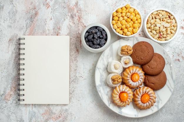 흰색 책상에 사탕과 견과류와 함께 상위 뷰 맛있는 쿠키 달콤한 케이크 쿠키 비스킷 너트