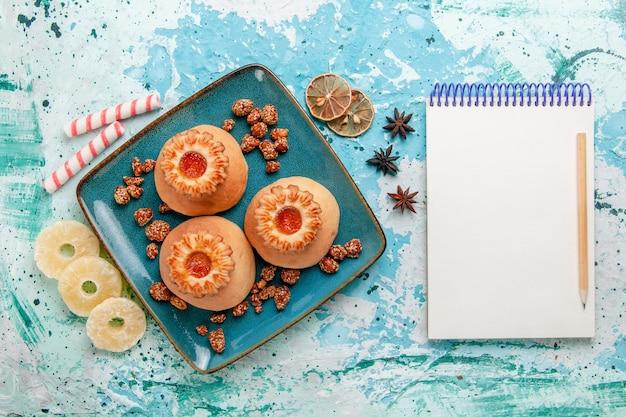 Vista dall'alto deliziosi biscotti con caramelle e blocco note su sfondo azzurro biscotto biscotto dolce zucchero colore