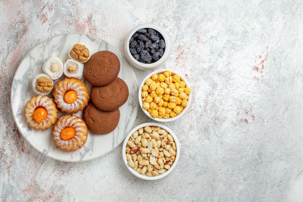 Top view delicious cookies with candies and nuts on the white background cake cookie biscuit sweet sugar tea
