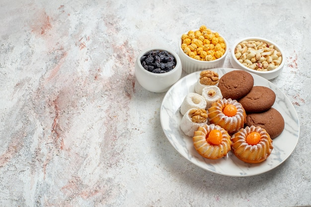 Top view delicious cookies with candies and nuts on white background sweet cake cookies biscuit nut