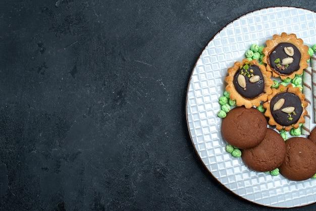 トップビュー灰色の背景にキャンディーとおいしいクッキービスケットシュガーベイクケーキパイティークッキー