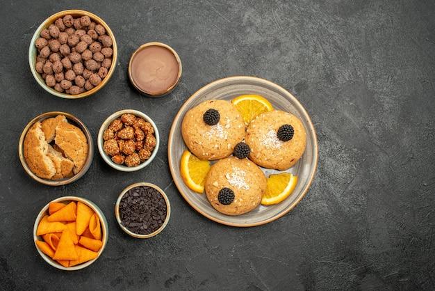 ダークグレーのデスククッキービスケットティースウィートケーキにチップスとナッツを添えたトップビューのおいしいクッキー