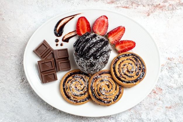 白いスペースにチョコレートケーキとイチゴとトップビューのおいしいクッキー