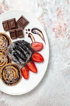 Вид сверху вкусного печенья с шоколадным тортом и клубникой на светлом белом пространстве