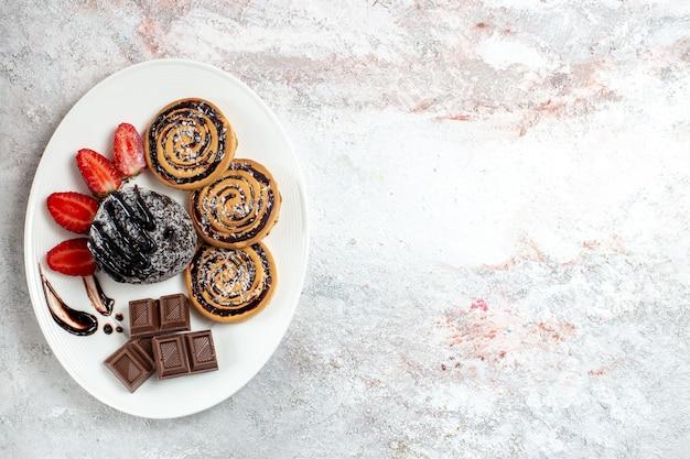白い机の上にチョコレートケーキとイチゴとトップビューのおいしいクッキー