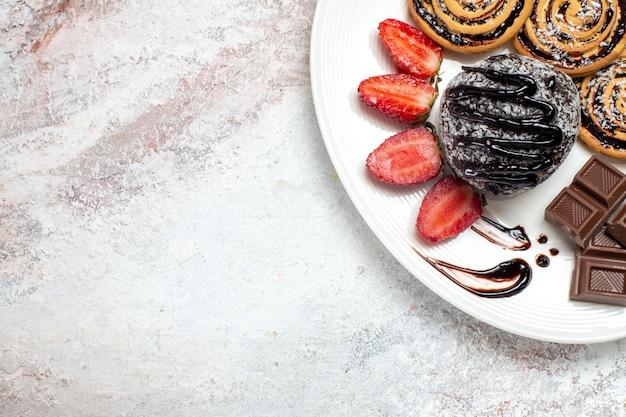 Вид сверху вкусного печенья с шоколадным тортом и клубникой на белом пространстве