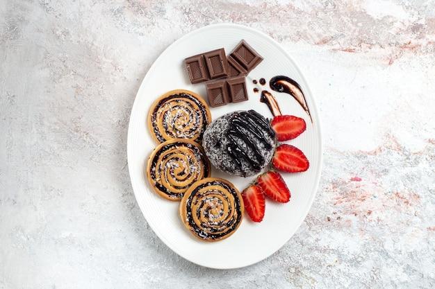 Vista dall'alto deliziosi biscotti con torta al cioccolato e fragole su uno spazio bianco