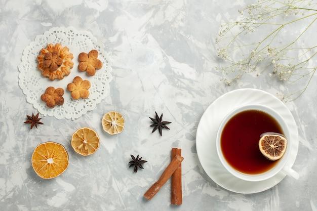Vista dall'alto deliziosi biscotti con cannella e tazza di tè sulle patatine fritte dolci del tè dello zucchero del biscotto della scrivania bianca chiara