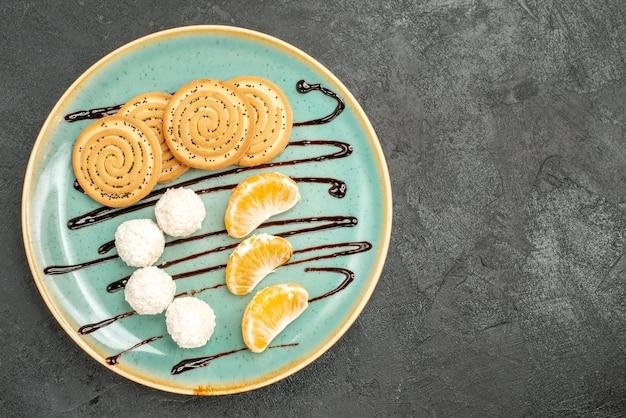 Vista dall'alto deliziosi biscotti con caramelle al cocco e frutta sulla scrivania grigia