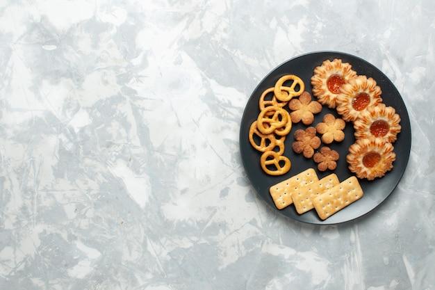 Вид сверху вкусного печенья с крекерами и чипсами внутри тарелки на легком белом настольном печенье, сахарном сладком чае