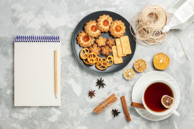 Вид сверху вкусного печенья с крекерами и чипсами внутри тарелки с чашкой чая на светлом белом столе, печенье, печенье, сахар, сладкий чай, чипсы