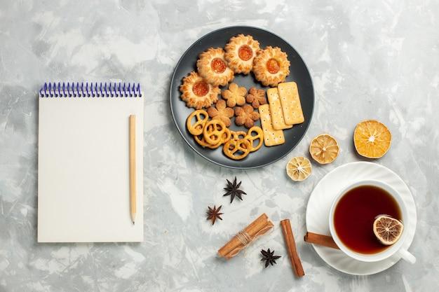 밝은 흰색 책상 쿠키 비스킷 설탕 달콤한 차 칩에 차 한잔과 함께 접시 안에 크래커와 칩이있는 상위 뷰 맛있는 쿠키