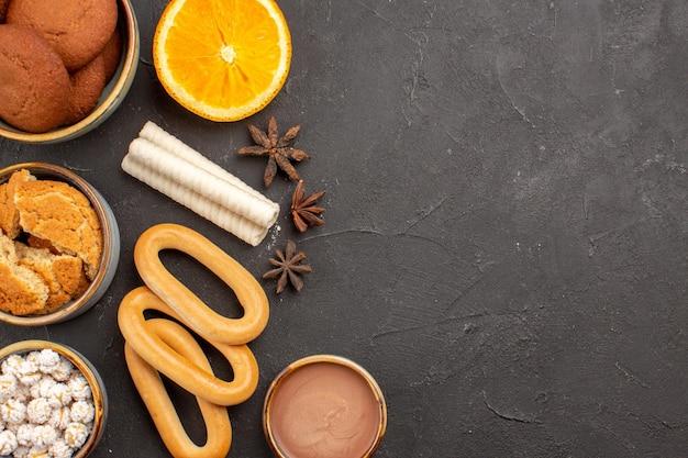 トップビューダークデスククッキービスケットシュガーデザートスウィートケーキにクラッカーとおいしいクッキー