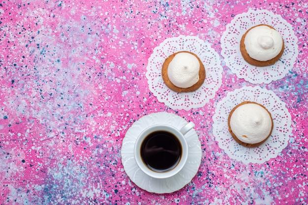 Вид сверху вкусного печенья со сливками и чашкой кофе на цветном столе, печенье, крем, сладкое