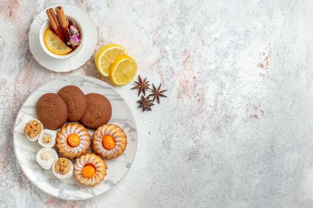 Вид сверху вкусное печенье с чашкой чая на белом фоне печенье, печенье, сахар, сладкий торт, чай