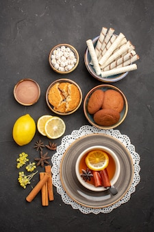 Вид сверху вкусного печенья с чашкой чая на темной поверхности печенье сладкий цитрусовый бисквит фруктовый сахар