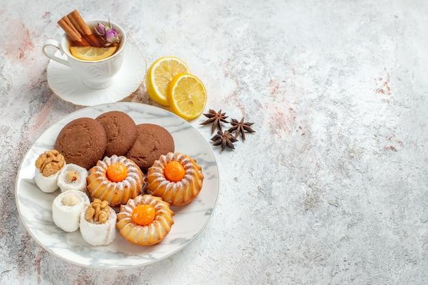上面図白い背景の上のお茶とおいしいクッキークッキービスケットシュガー甘いケーキティー